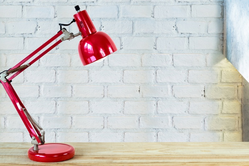 Red lamp on wooden table top over brick wall background/ Interior decoration concept
